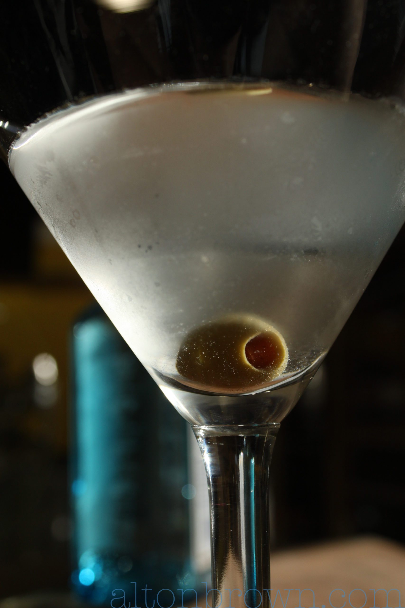 Alton Brown's classic martini in a martini glass with a green olive.