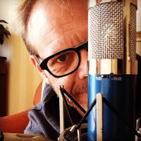 Alton Brown peeks out from behind his microphone while recording The Alton Browncast.