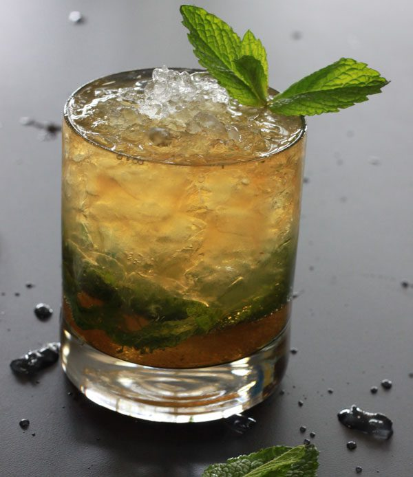 Alton Browns mint julep with crushed ice in a rocks glass and a mint sprig garnish.