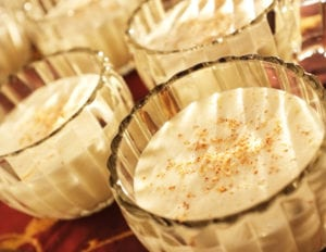 Aged eggnog in glass goblets topped with eggnog.