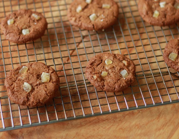 Triple ginger gingersnap cookies on a wire cooling rack.