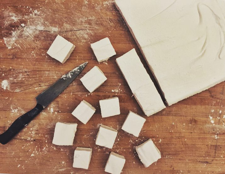 Homemade vanilla marshmallows on a wooden cutting board.