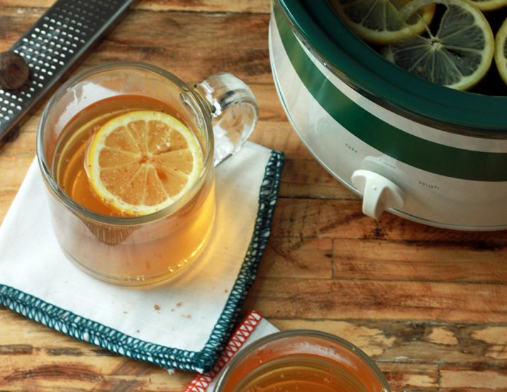 Slow-cooker hot toddy in a clear mug garnished with a lemon slice.