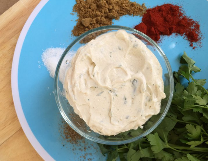 Savory Greek yogurt dip in a clear bowl set on a blue place surrounded by spices and herbs.