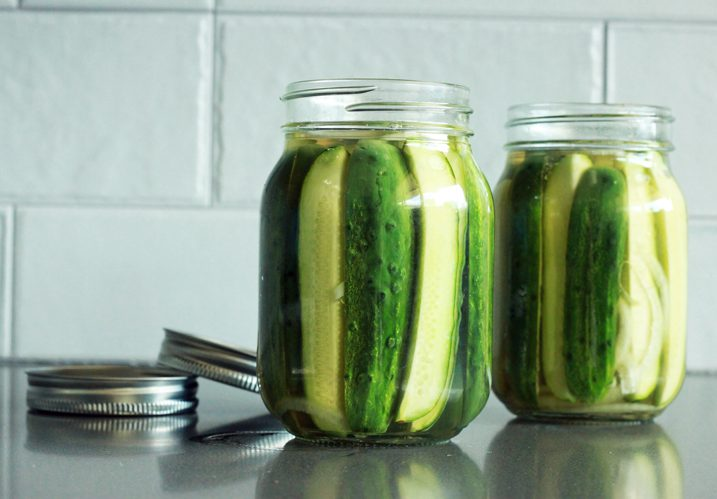 Homemade pickles packed vertically in two mason jars.