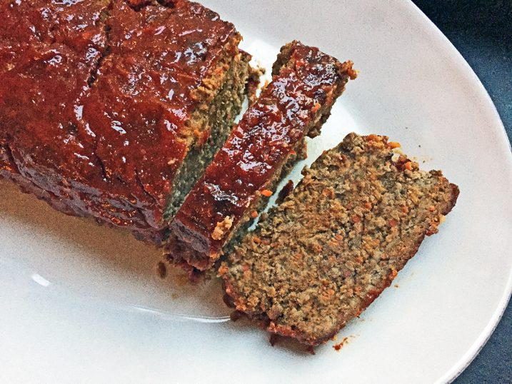 Whole meatloaf on a white platter with a slice removed.