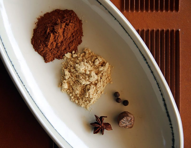 Pumpkin pie spice ingredients in a white, oval dish.