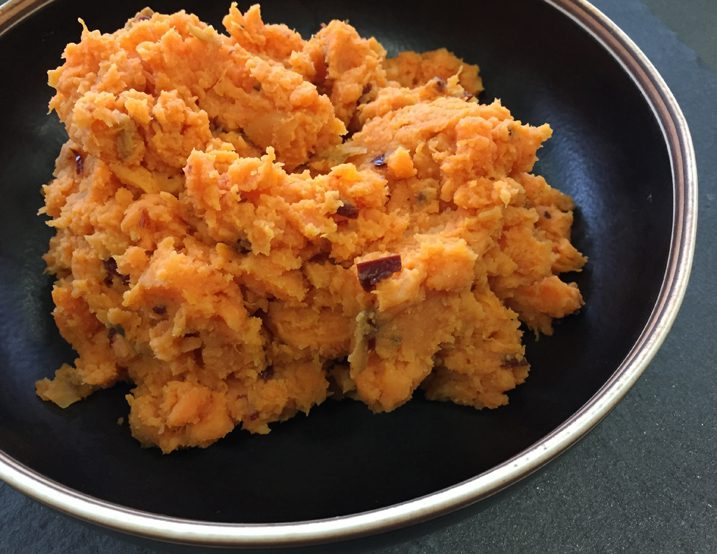Chipotle smashed sweet potatoes in a black bowl.