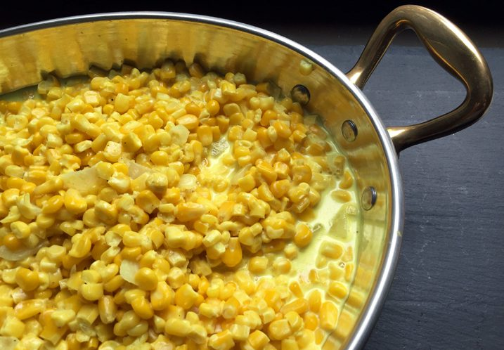 Rosemary creamed corn in a metal saucier.