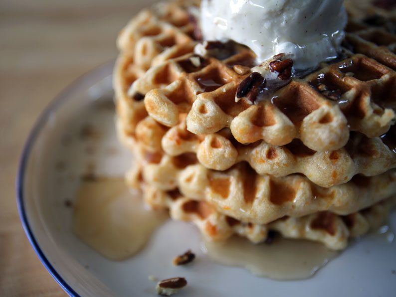 Stacked sweet potato waffles topped with pecans, syrup, and whipped cream.