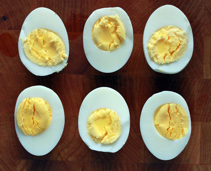 Eggs under pressure cut in half with the yolks facing upwards.
