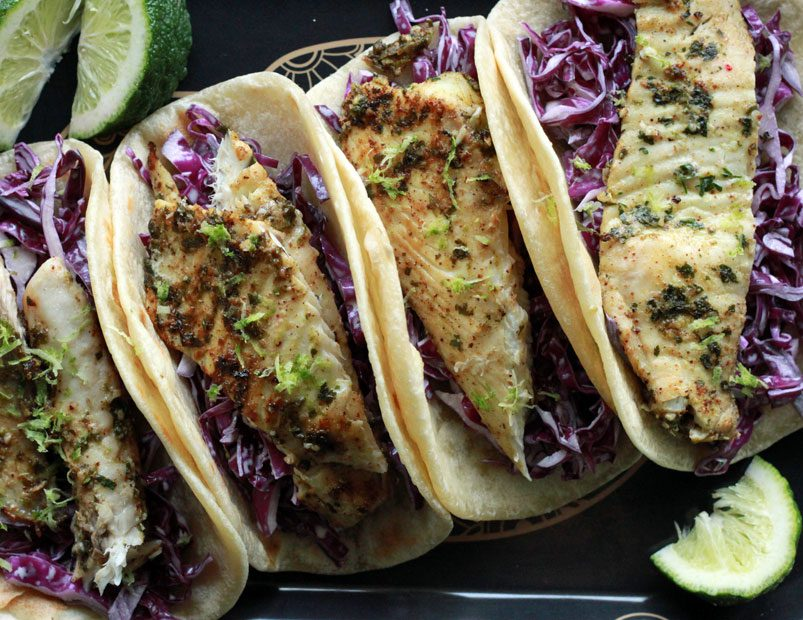 Tequila lime fish tacos with creme and red cabbage slaw lined up on a serving platter.