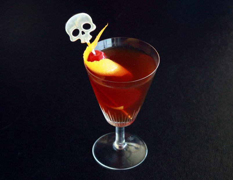 Rise and grind cocktail in a stemmed glass garnished with a maraschino cherry, orange peel, and a skull swizzle stick.