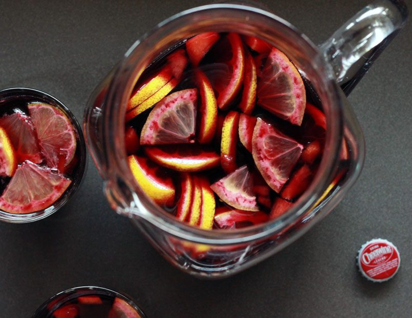 Cheerwine sangria and quartered oranges in a glass pitcher.