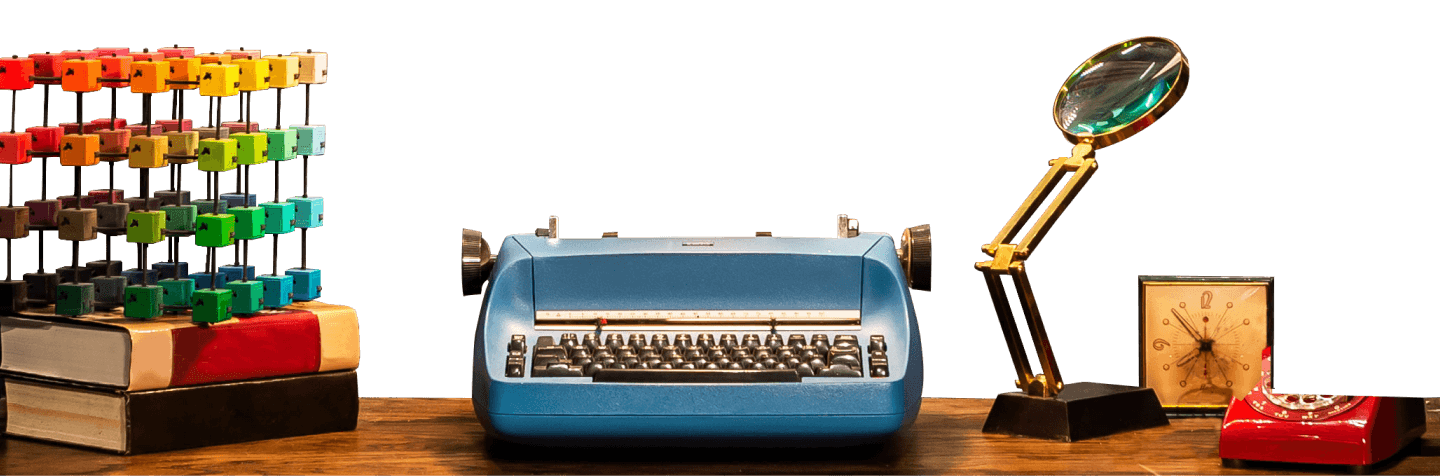 Blue vintage typewriter on a desk with a magnifying glass, and a clock