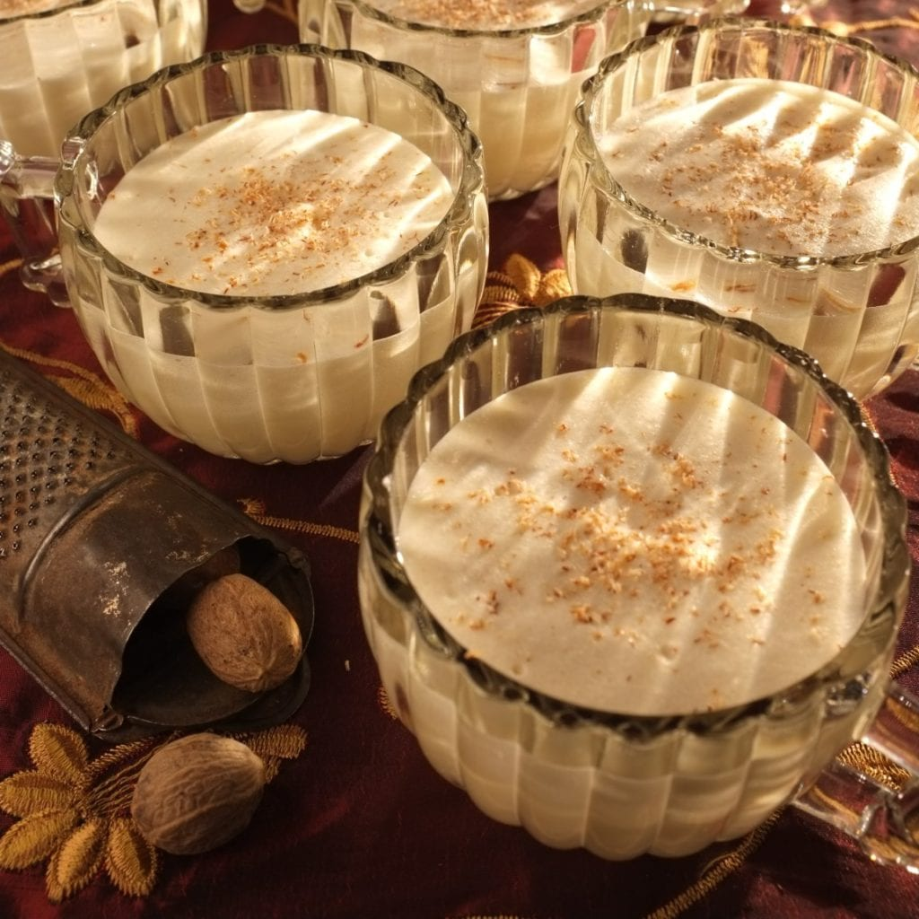 Eggnog in glass goblets topped with freshly grated nutmeg.