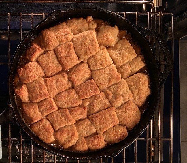 Peach cobbles in a cast-iron skillet.