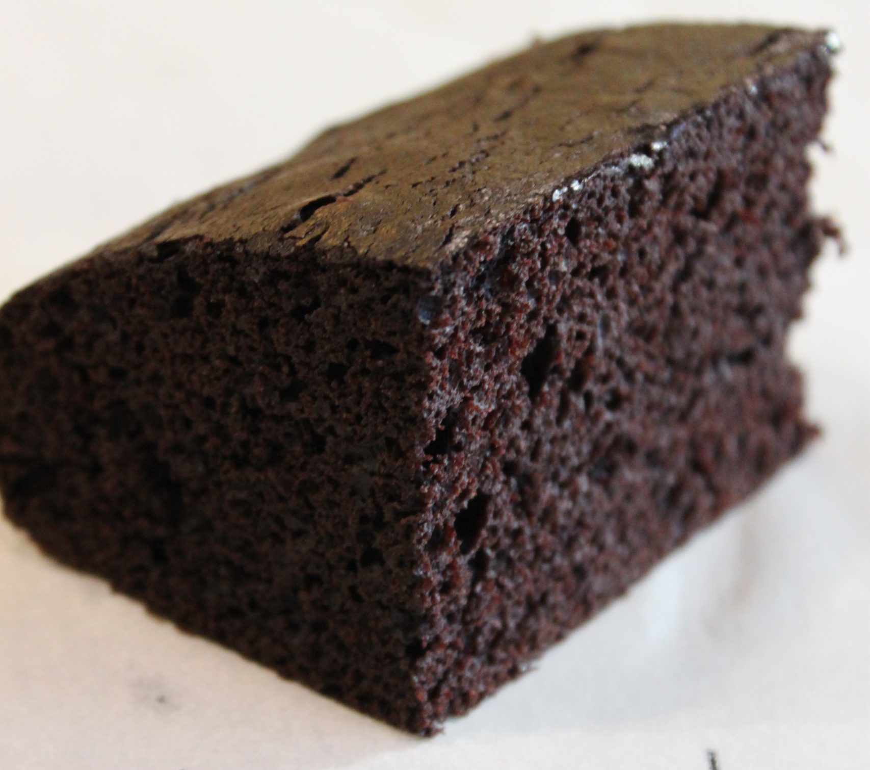 A square slice of Alton Browns chocolate devils food cake.