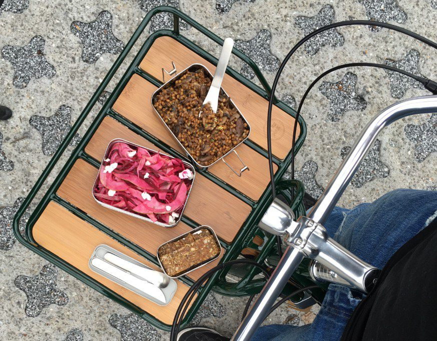 Mushroom wheat berry salad in a rectangle tin in a bicycle basket.