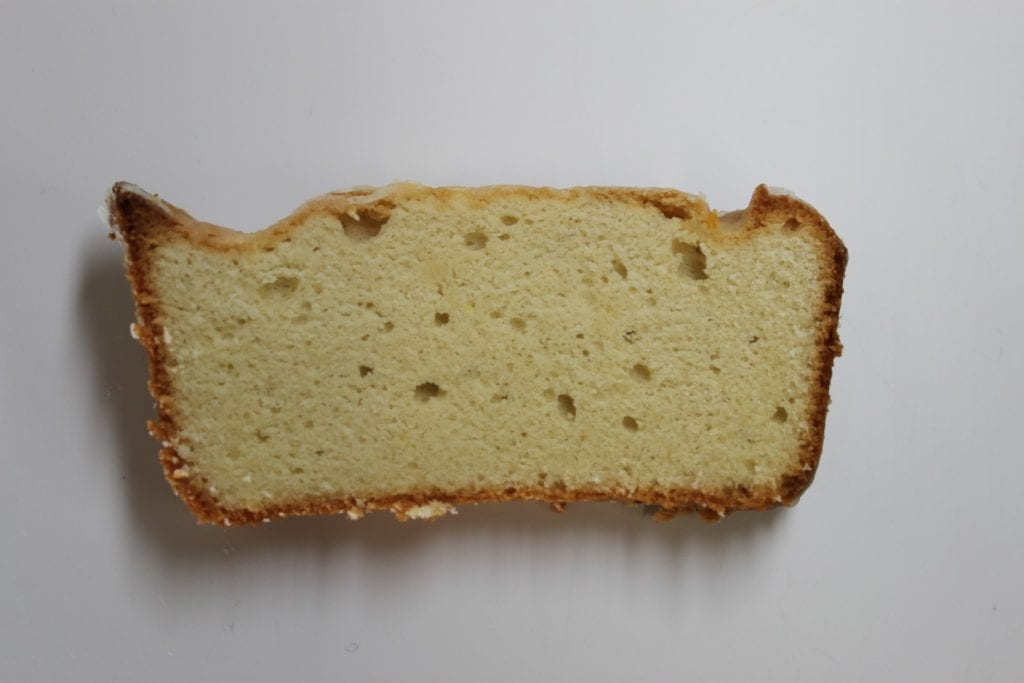 A slice of pound cake on a white surface on the set of Good Eats.