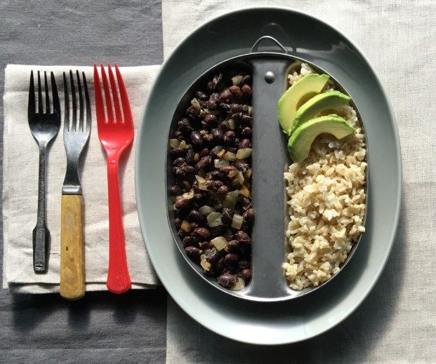 Black beans and brown rice plated with sliced avocado.