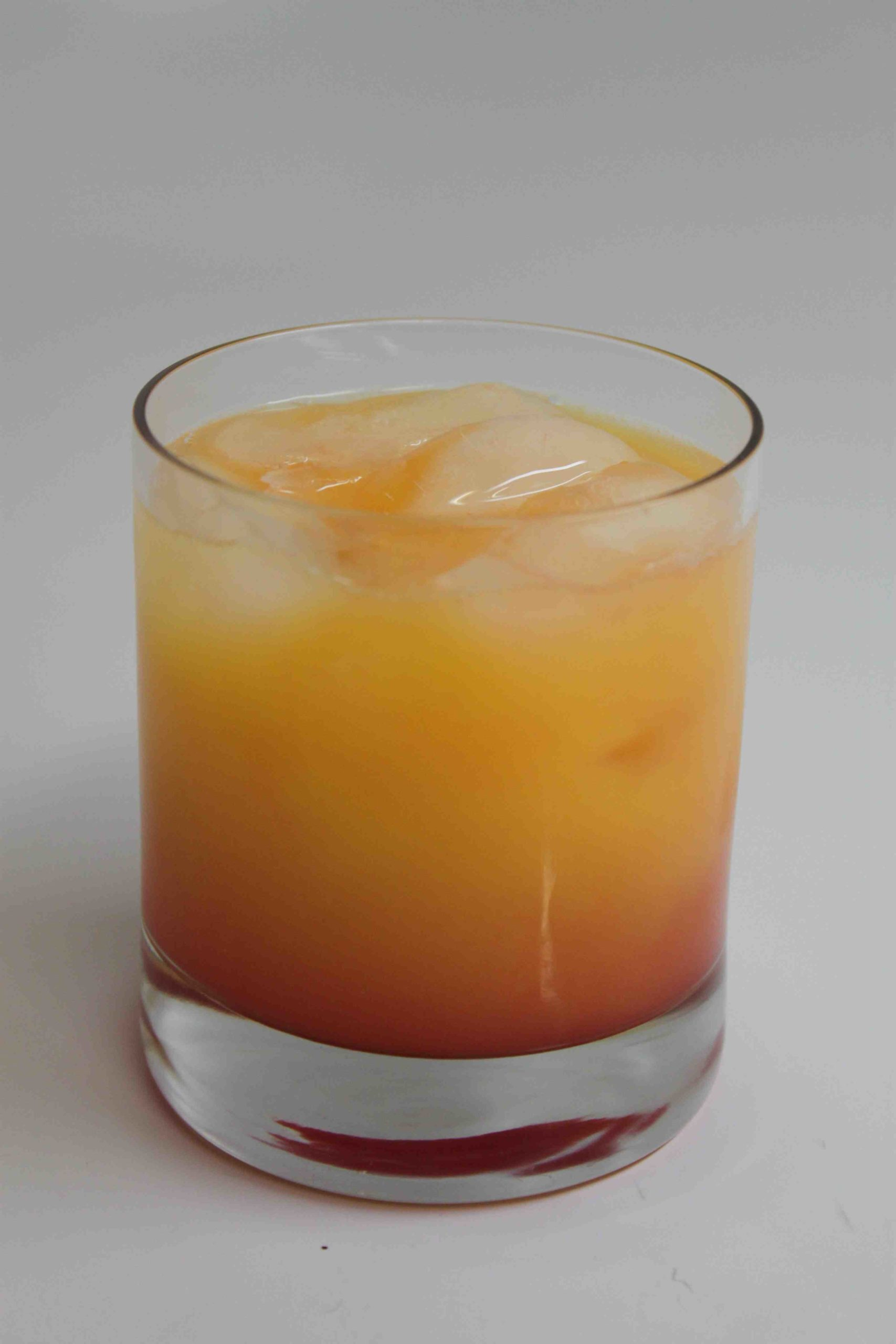 Tequila sunrise with ice in a rocks glass.