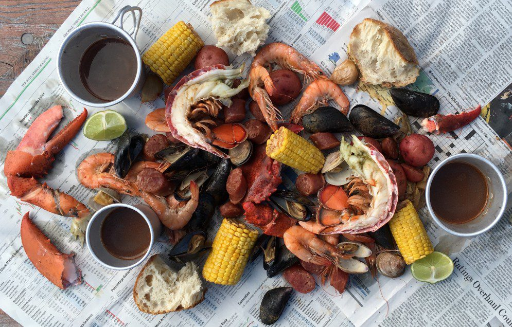 Lowcountry boil with lobster and mussels on a newspaper-lined picnic table.