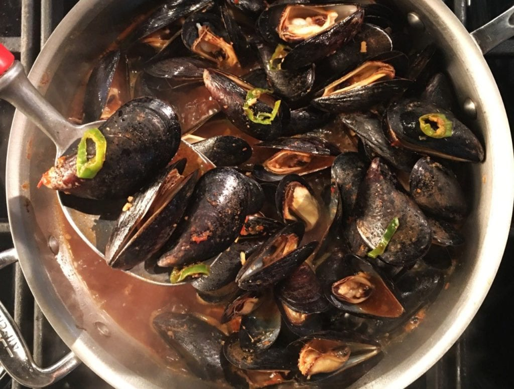 Mussels o miso in a large pot on the stove.