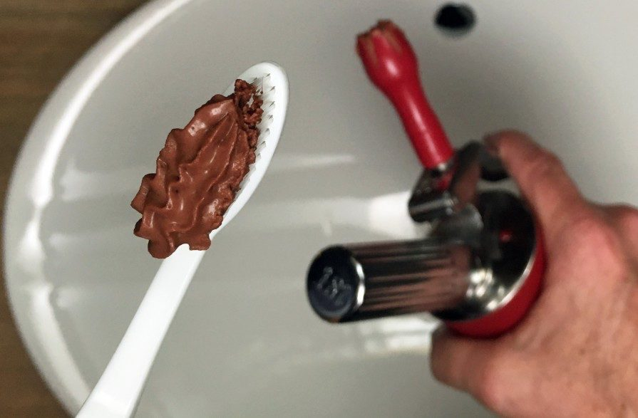 Foam whipper chocolate mousse on a white spoon.