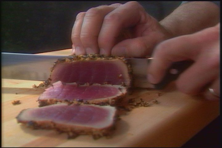 Alton Brown slices chimney tuna loin on the set of Good Eats.