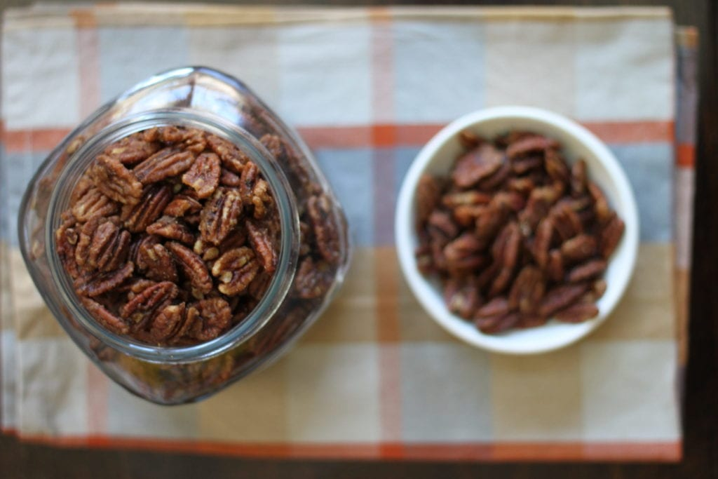 Alton Brown's spicy pecans in a glass jar and a white ramekin.