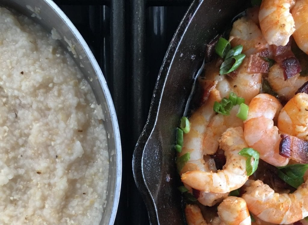 Grits and shrimp set side by side on a stove.