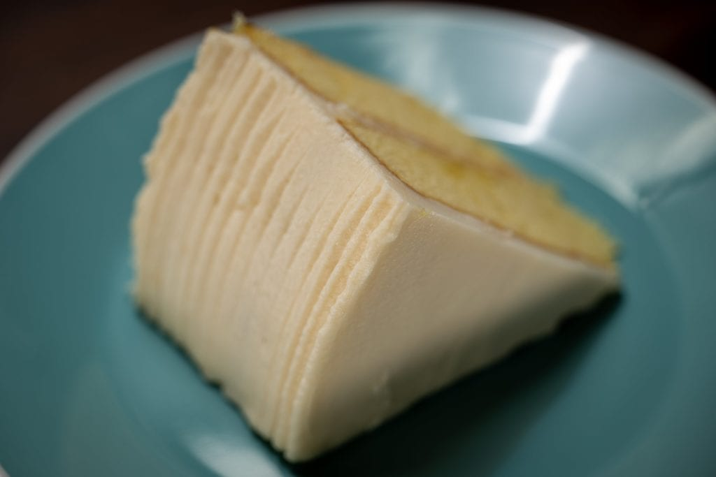American Butter(milk)cream on a slice of Alton Brown's gold cake plated on teal plate.