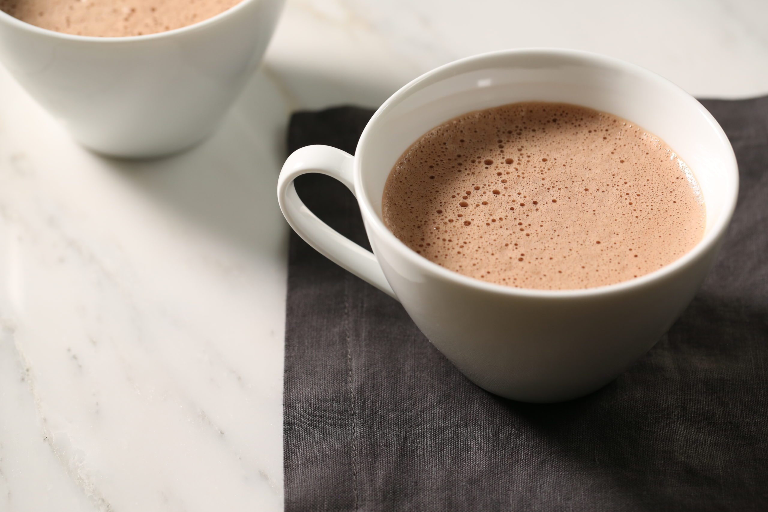 Hot cocoa in a white mug sitting on a black napkin.