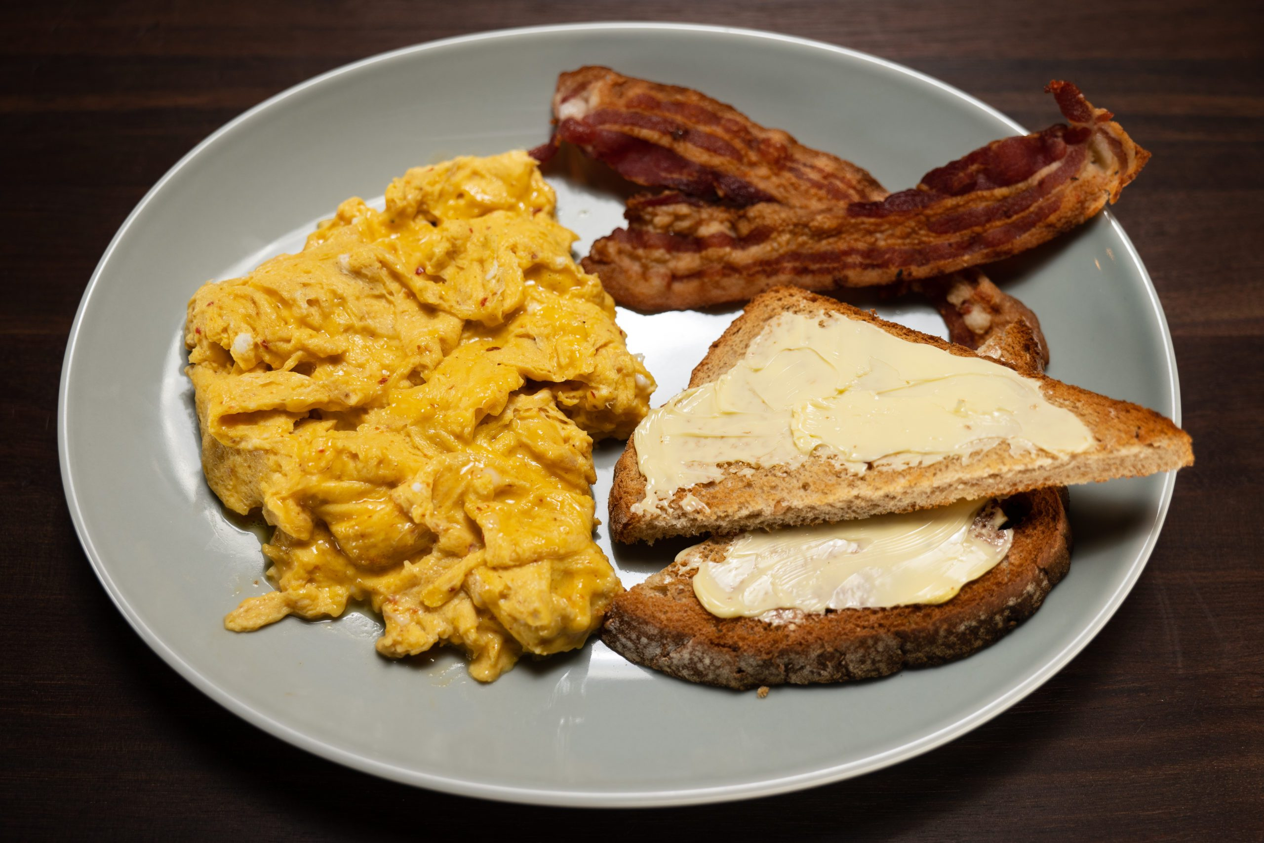 20 second scrambled eggs with harissa on a grey plate with bacon and buttered toast.