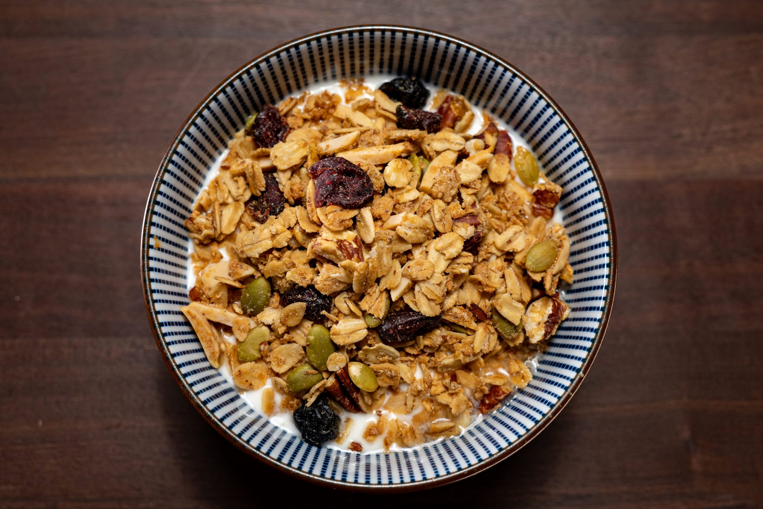 Alton Brown's granola in a striped bowl with milk