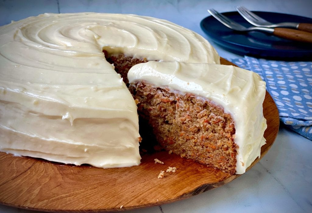 A slice of classic carrot cake being removed from a whole carrot cake.