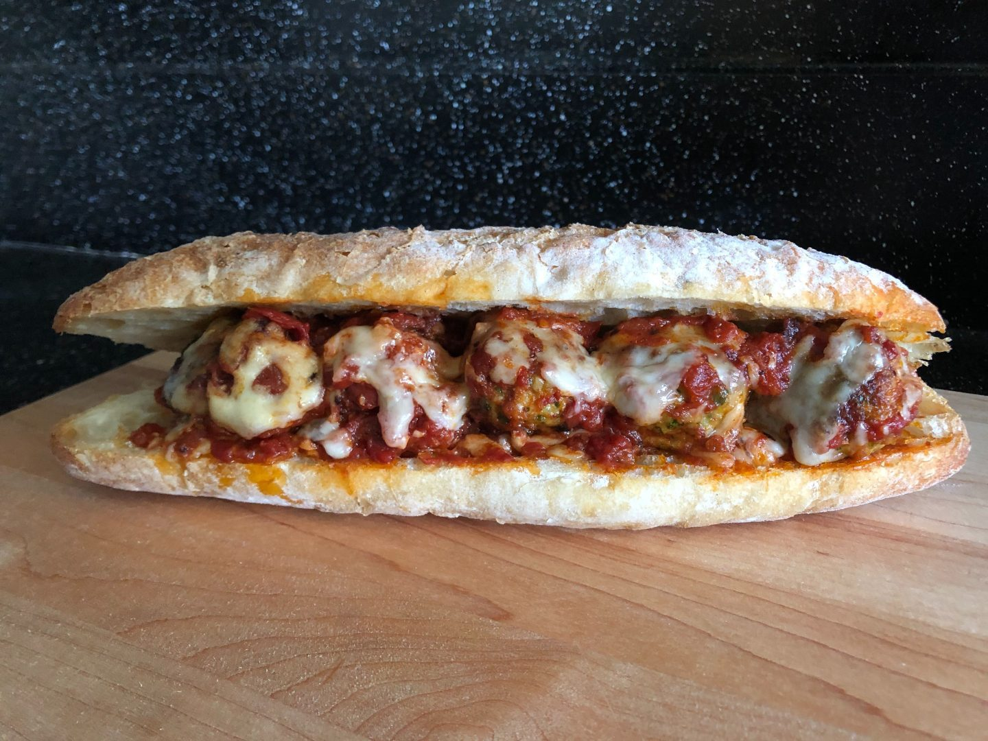 Chicken Parmesan meatballs in a meatball sub on a wooden countertop.