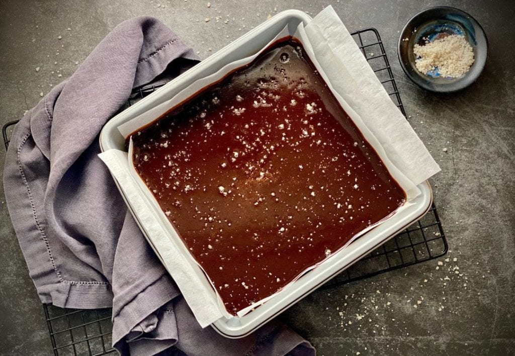 Homemade salted caramels cooling in a parchment paper-lined baking dish.
