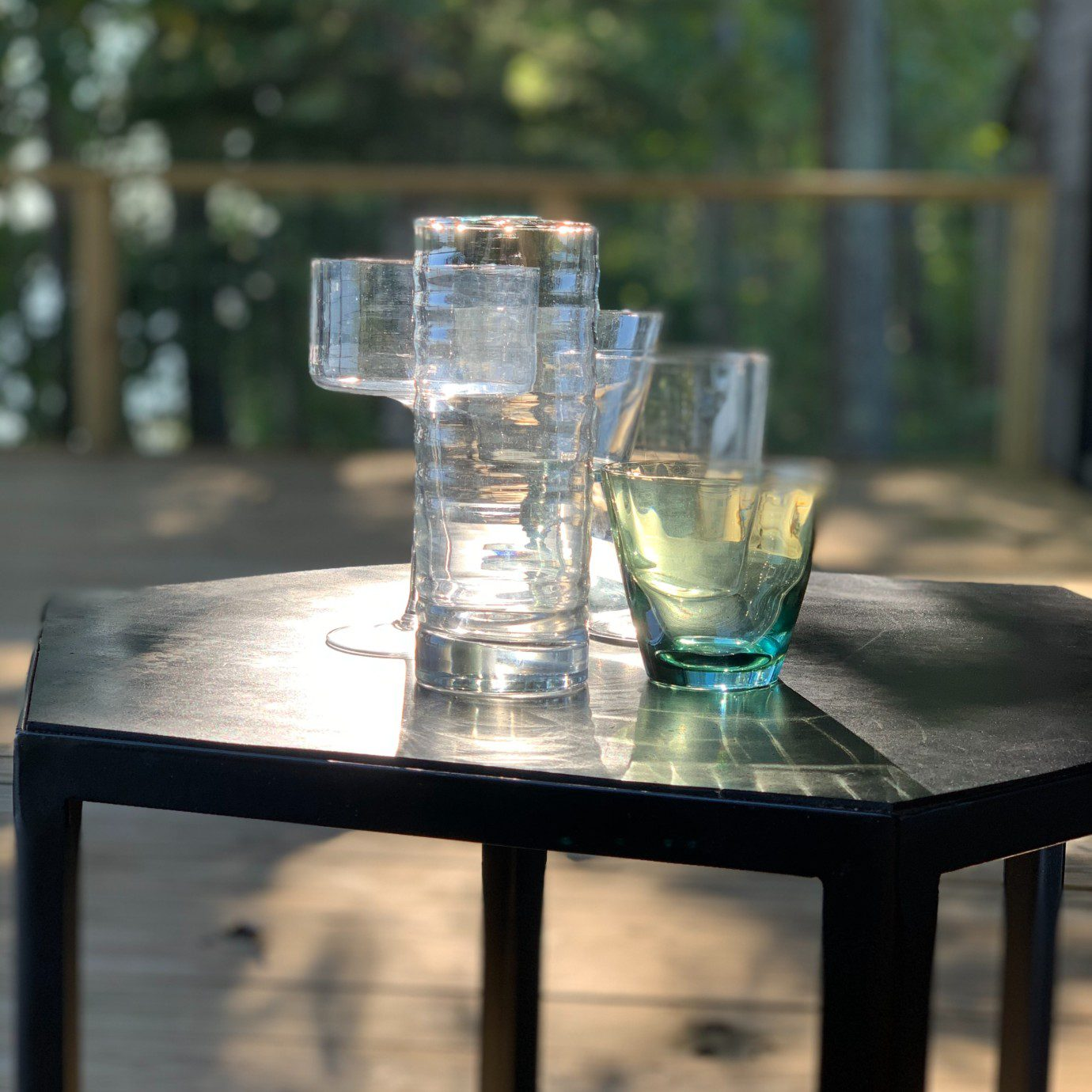 Alton Brown's cocktail glasses displayed outdoors on a black end table.