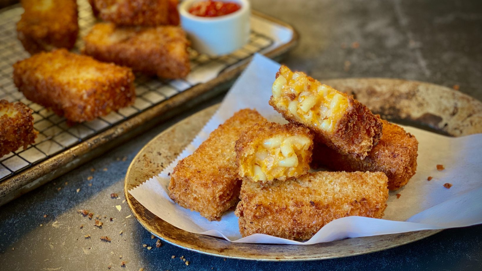 Fried mac and cheese sticks on a paper towel-lined plate.