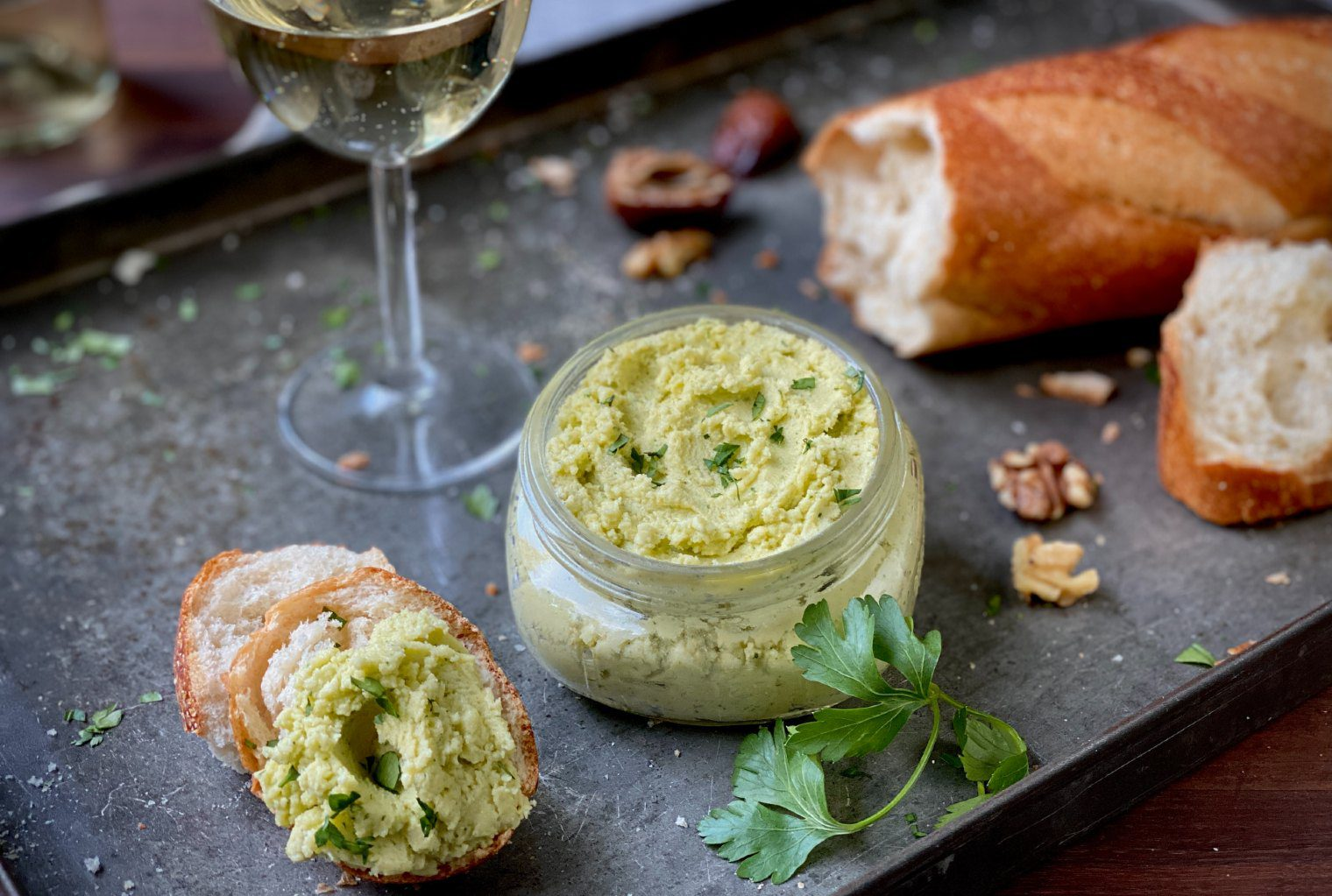 5-ingredient cheese spread with parsley in a glass jar served with a baguette and a glass of white wine.