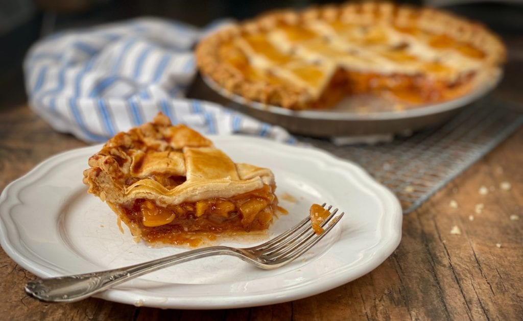 Frozen peach pie slice on a plate with a fork.