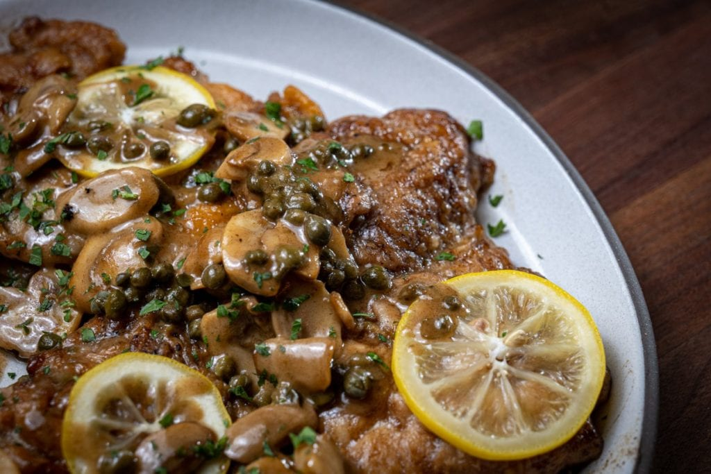 Good Eats chicken piccata on a white platter garnished with lemon slices.