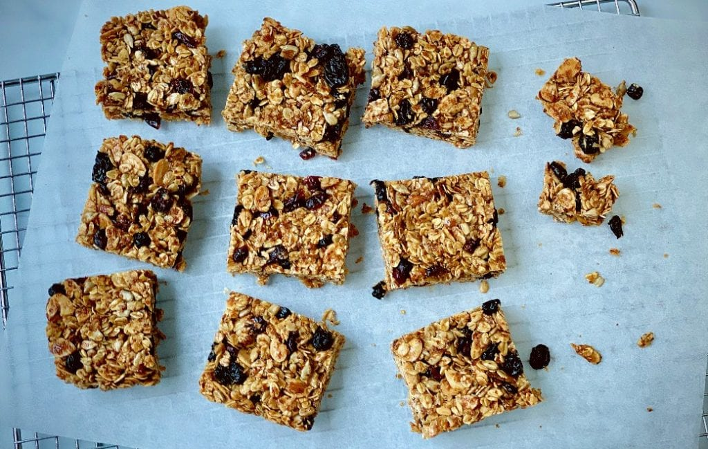 Homemade granola bars cut into squares on a piece of parchment paper.