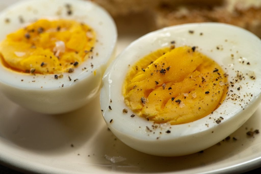 Hard not-boiled egg halves sprinkled with salt and freshly ground black pepper.