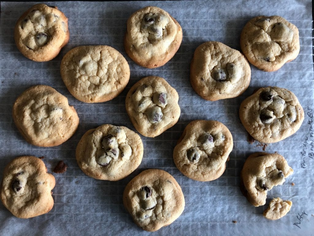 The Puffy chocolate chip cookies on a parchment paper-lined wire rack.