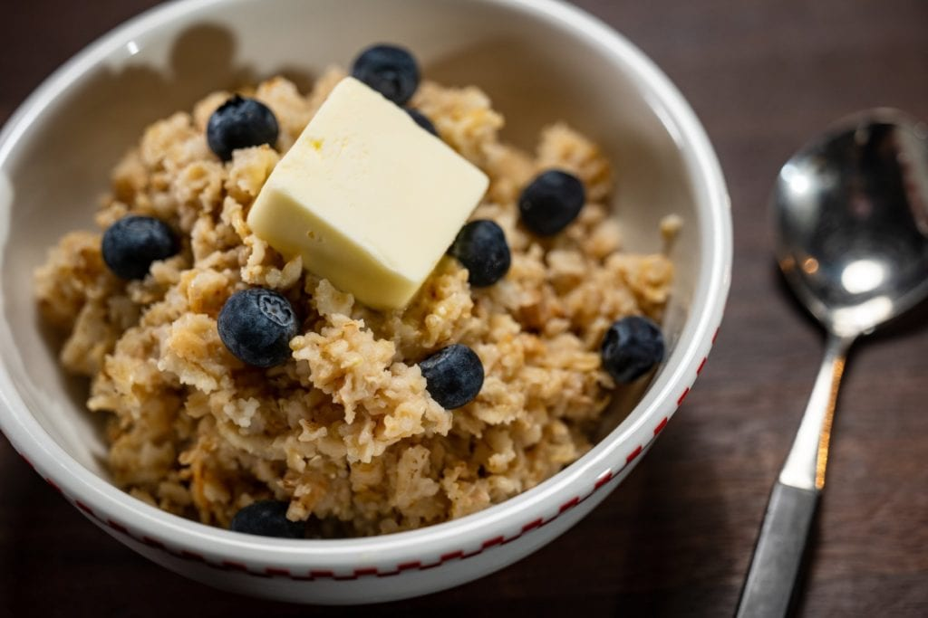 Jussst right oatmeal in a white bowl with blueberries and butter.