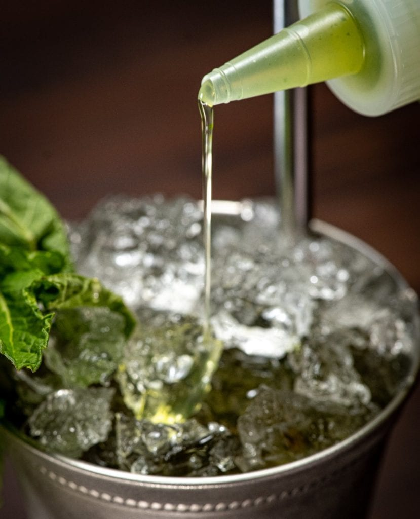 Simple mint syrup in a squeeze bottle drizzled into a mint julep cup filled with crushed ice and garnished with a mint sprig.