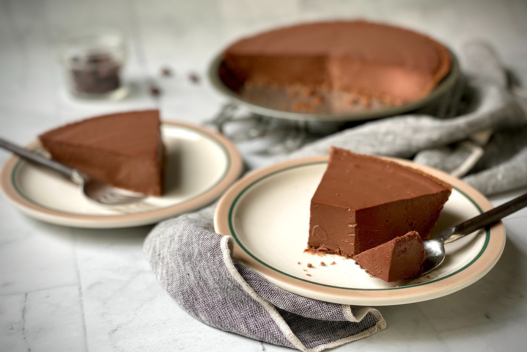 Dairy-free chocolate pie slice on a plate with a bite missing.